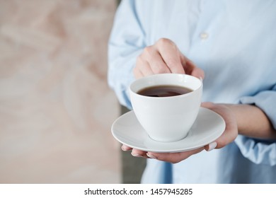 Woman holding cup of coffee. Female hands with cup of black tea on beige background. Close up