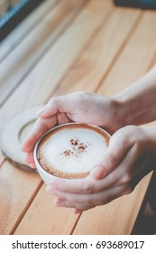 Woman is holding a cup coffee in hand with vintage color tone filter background