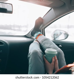 Woman is holding cup of coffee inside of car. Travel lifestyle. Legs on dashboard