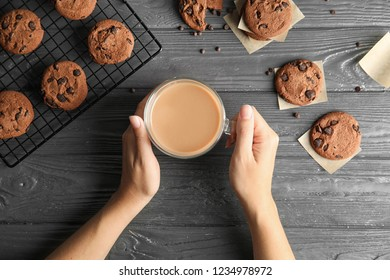 Woman holding cup of coffee near tasty chocolate chip cookies on wooden background, top view