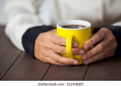 Woman holding a cup of coffee on wooden table