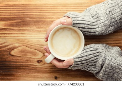 the woman is holding a cup of coffee on a wooden table