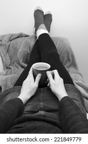 Woman holding a cup of coffee or tea, relaxing on the couch with her feet up - monochrome processing