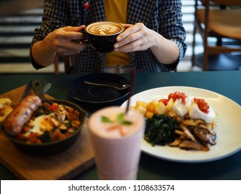 Woman holding a cup of hot latte at nice vintage cafe. People drinking coffee in brunch concept, blurred foreground of Strawberry smoothie yogurt, Oven baked egg with sausage, Eggs Benedict.