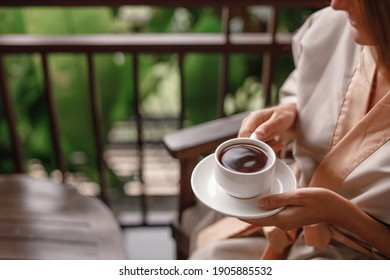 Woman holding cup of hot steaming drink tea on the  balcony with tropical view