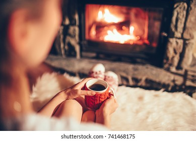 Woman holding a cup of tea by the Christmas fireplace. Woman relaxes by warm fire with a cup of hot drink and warming up her feet in woollen socks. Close up on feet. Winter, Christmas holidays concept