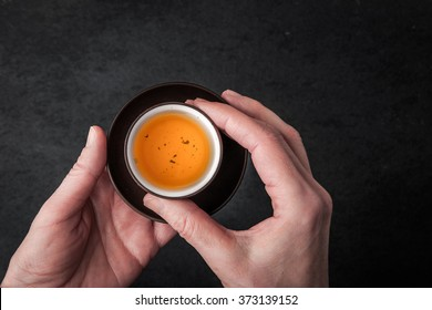 A woman holding a cup of tea horizontal