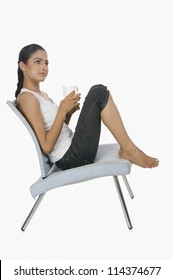 Woman holding a cup of tea and thinking on a chair