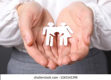 Woman holding cutout paper family, closeup. Life insurance concept