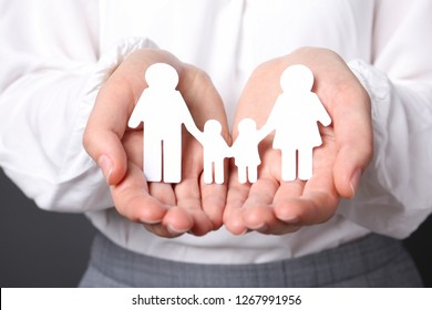 Woman holding cutout paper family, closeup. Life insurance concept