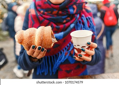 Woman holding czech traditional delicious trdelnik and hot wine closeup