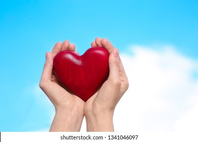 Woman holding decorative heart in hands on color background, space for text
