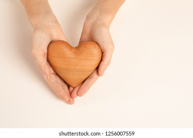 Woman holding decorative heart on white background, top view with space for text