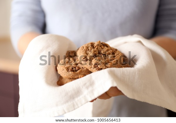 Woman holding delicious oatmeal cookies with chocolate chips, closeup