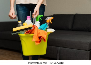 A woman is holding detergents in a bucket on the background. Woman is ready to clean house. A housewife is cleaning house
