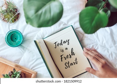 Woman holding a diary with inscription today is a fresh start with plants and succulents on white blanket. Homy, comfortable flat lay with inspirational quote