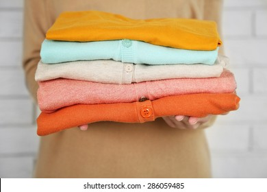 Woman holding different clothes, on bricks wall background