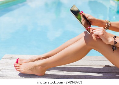 Woman holding digital tablet outdoors by the swimming pool
