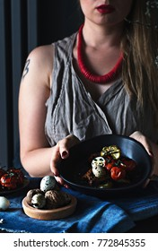 Woman is holding a dish: hard-boiled quail eggs on toast with baked cherry tomatoes and pickled cucumber.