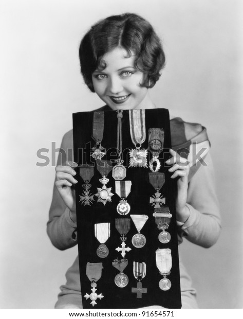Woman holding display of medals