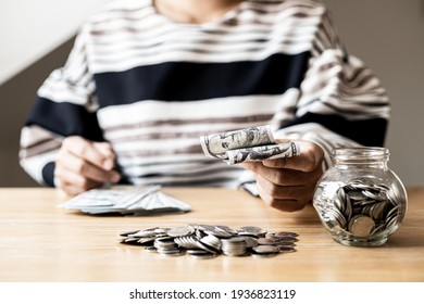 Woman holding dollar bills, on the table a large pile of coins and banks, she is managing to divide the money to save money and invest it to make it grow even more. Saving money and investing concept.