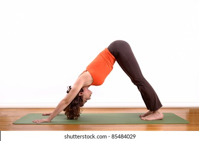woman holding a downward facing dog pose on a mat