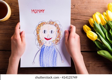 Woman holding drawing of her from her daugter. Tulips.