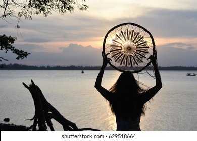 Woman holding dream catcher on the beach