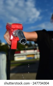 woman holding a dripping red gas petrol hose nozzle