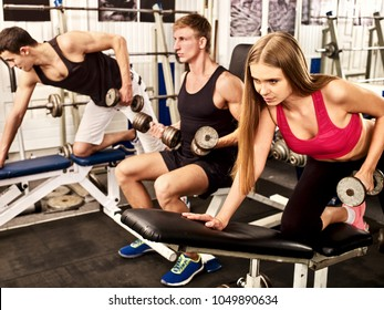 Woman holding dumbbell workout at gym. Cropped shot of of middle section of bare belly. Friends men on background. Body that you want concept. Girl keeps herself in good shape.