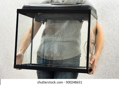woman holding empty aquarium to restart it at home