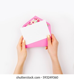 Woman holding a empty card and pink envelope. Beautiful  mock up. Flat lay, top view