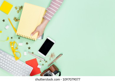 Woman holding a empty notebook on table top view. Female blogger working desk