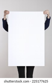 A woman holding a empty(blank) white paper poster or board.