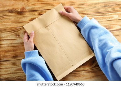 Woman holding envelope on wooden background