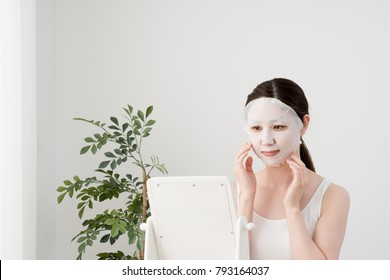 A woman holding a face mask, a mirror