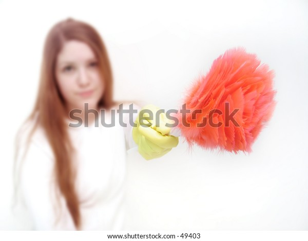 Woman holding a feather duster into the camera. Focus on rubber glove and duster.