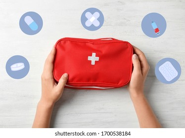 Woman holding first aid kit on wooden background, top view