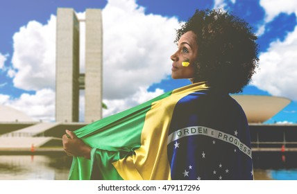 Woman holding the flag of Brazil in Brasilia