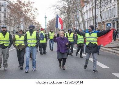 "A woman holding a flag with protesters in front of  Bastille square during the ""Yellow Vests"" antigovernment protest in the French capital. Paris, France - December 8, 2018"
