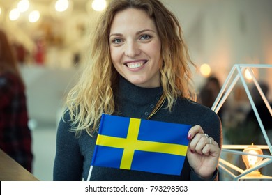 Woman holding a flag of Sweden. Portrait Scandinavian woman.