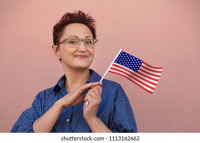 Woman holding flag of United States of America USA.  Nice portrait of middle aged American lady 40 50 years old with a national USA flag. Learning English language. Visit USA concept.