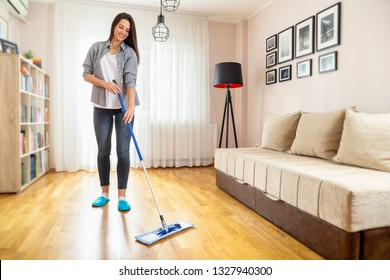 Woman holding a floor wiper and wiping floor, keeping the daily home hygiene and doing housework