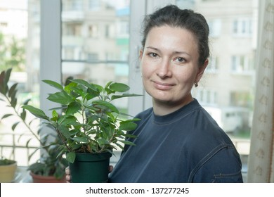 Woman holding flower pot, with houseplant