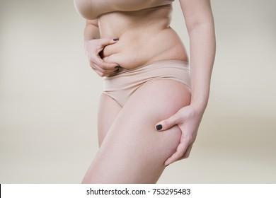 Woman holding fold of skin, cellulite on female body, beige background, studio shot