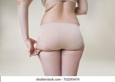 Woman holding fold of skin on buttocks, cellulite on female body, beige background, studio shot