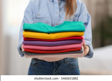 Woman holding folded clean clothes indoors, closeup. Laundry day