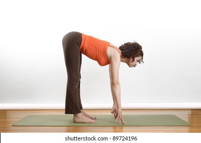 Woman holding a forward bend extension yoga position on a green mat.