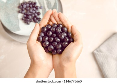 Woman holding fresh acai berries over table, top view