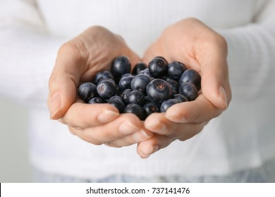 Woman holding fresh acai berries, closeup
